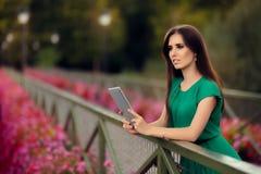 有数字式片剂的妇女在有花的一座桥梁 免版税库存照片
