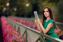 有数字式片剂的妇女在有花的一座桥梁 免版税图库摄影