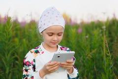 有数字式片剂的小女孩在自然 免版税图库摄影