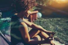 有数字式片剂的性感的黑人卷曲女孩在公园 免版税库存图片
