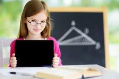 有数字式片剂的聪明的矮小的女小学生在教室 免版税图库摄影