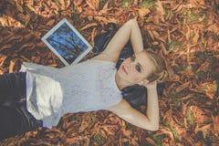 有数字式片剂的青少年的女孩在户外秋天 库存图片