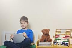 有数字式片剂计算机的微笑的愉快的孩子在家 库存图片