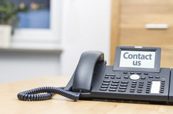 有数字显示的电话在木服务台上 库存图片