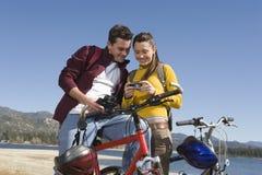 有数字照相机的山骑自行车的人反对蓝天 库存照片