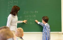 有数学老师文字的男小学生在粉笔板 免版税库存图片