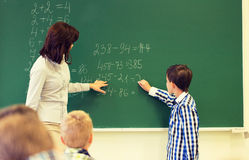 有数学老师文字的男小学生在粉笔板 库存图片
