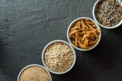 有整个五谷碳水化合物、燕麦、糙米、种子、奎奴亚藜和整个五谷面团的碗 整个五谷谷物 免版税库存照片