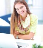 有文件的妇女坐有膝上型计算机的书桌 库存照片