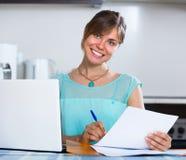 有文件的微笑的妇女在厨房 免版税库存图片