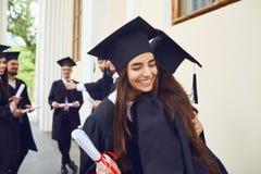 有文凭的女性毕业生在他们手拥抱 免版税图库摄影