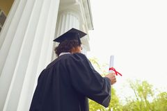 有文凭的愉快的毕业生在手中在大学背景 免版税库存照片