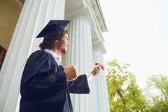有文凭的愉快的毕业生在手中在大学背景 免版税图库摄影