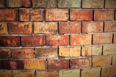 有文字的红砖墙壁 免版税库存照片