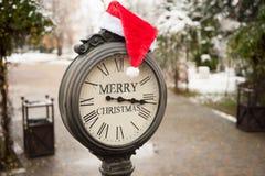 有文本圣诞快乐和圣诞老人帽子的葡萄酒时钟在他们室外在冬天纽约 免版税库存图片