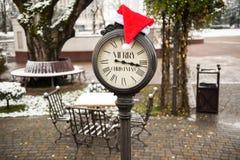 有文本圣诞快乐和圣诞老人帽子的葡萄酒时钟在他们室外在冬天镇 免版税库存图片