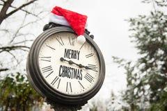 有文本圣诞快乐和圣诞老人帽子的葡萄酒时钟在他们室外在冬天 免版税库存照片