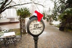 有文本圣诞快乐和圣诞老人帽子的葡萄酒时钟在他们室外在镇冬天街道 免版税库存图片