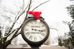 有文本圣诞快乐和圣诞老人帽子的葡萄酒老时钟在他们室外在冬天 库存照片