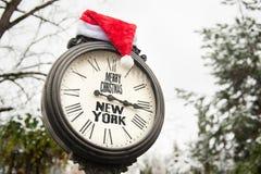 有文本圣诞快乐纽约和圣诞老人帽子的葡萄酒时钟在他们室外在冬天 库存照片