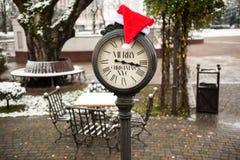 有文本圣诞快乐纽约和圣诞老人帽子的葡萄酒时钟在他们室外在冬天 图库摄影