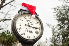 有文本新年快乐纽约和圣诞老人帽子的减速火箭的老时钟在他们户外在冬天 库存照片