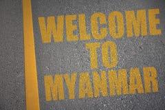 有文本欢迎的柏油路到在黄线附近的缅甸 库存照片