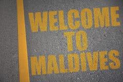 有文本欢迎的柏油路向在黄线附近的马尔代夫 免版税库存图片