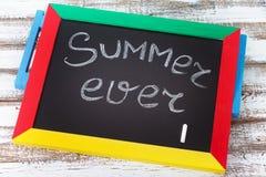 有文本的黑板它是夏时,辅助部件太阳镜,帽子,在木甲板的毛巾 库存照片