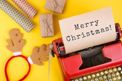 有文本& x22的红色打字机; 圣诞快乐! & x22; 礼物盒和包装纸在黄色背景 库存图片