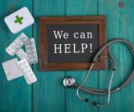 有文本& x22的黑板; 我们可以帮助! & x22; 药片和听诊器在蓝色木背景 库存照片