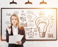 有文件和想法的妇女在whiteboard,被定调子 免版税库存图片