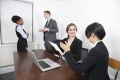 有文件和膝上型计算机的不同种族的女性,当同事交谈在背景中时 免版税图库摄影