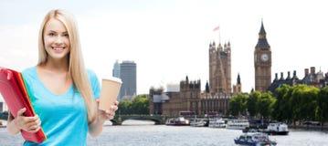 有文件夹和咖啡杯的微笑的学生女孩 免版税库存照片