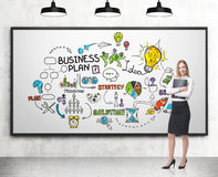 有文件夹的妇女和在whiteboard的经营计划 免版税库存图片