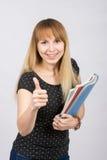 有文件夹的少妇在手上愉快地微笑和显示拇指的 免版税库存图片