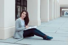 有文件夹的微笑的十几岁的女孩在uniersity的大厦之外 库存图片