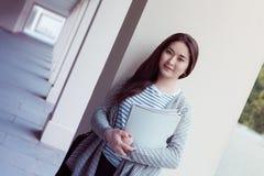 有文件夹的微笑的十几岁的女孩在uniersity 免版税库存照片