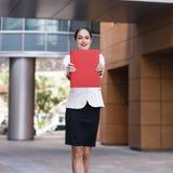 有文件夹的愉快的年轻女商人 免版税图库摄影