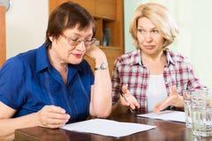 有文件的两名哀伤的年长妇女 免版税库存图片