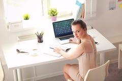 有文件的妇女坐书桌和膝上型计算机 图库摄影