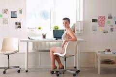 有文件的妇女坐书桌和膝上型计算机 免版税库存照片