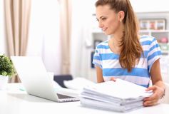 有文件的妇女坐书桌 免版税图库摄影