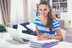 有文件的妇女坐书桌 免版税库存图片