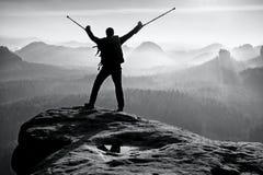 有断腿的远足者在麻醉器 有医学拐杖的游人在头上达到了山峰 图库摄影
