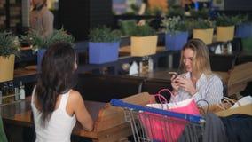 有断裂和使用智能手机的朋友在咖啡馆在购物中心在购物以后 免版税库存图片