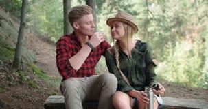 有断裂在森林和喝茶的微笑的夫妇 免版税库存照片