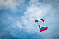 有斯洛文尼亚旗子的在斯洛文尼亚的颜色的跳伞运动员和降伞 免版税图库摄影