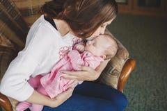 有新出生的女婴的愉快的母亲她的胳膊的 免版税库存照片