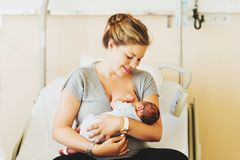 有新出生的婴孩的愉快的年轻母亲在医院 库存照片